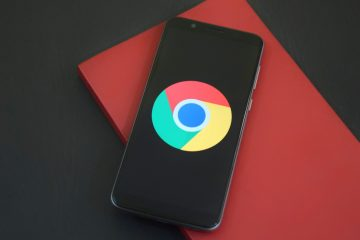 Smart Phone with google logo resting on a red notebook on a black table